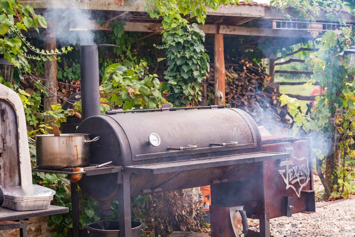 A well used offset smoker in a backyard in front of a log store