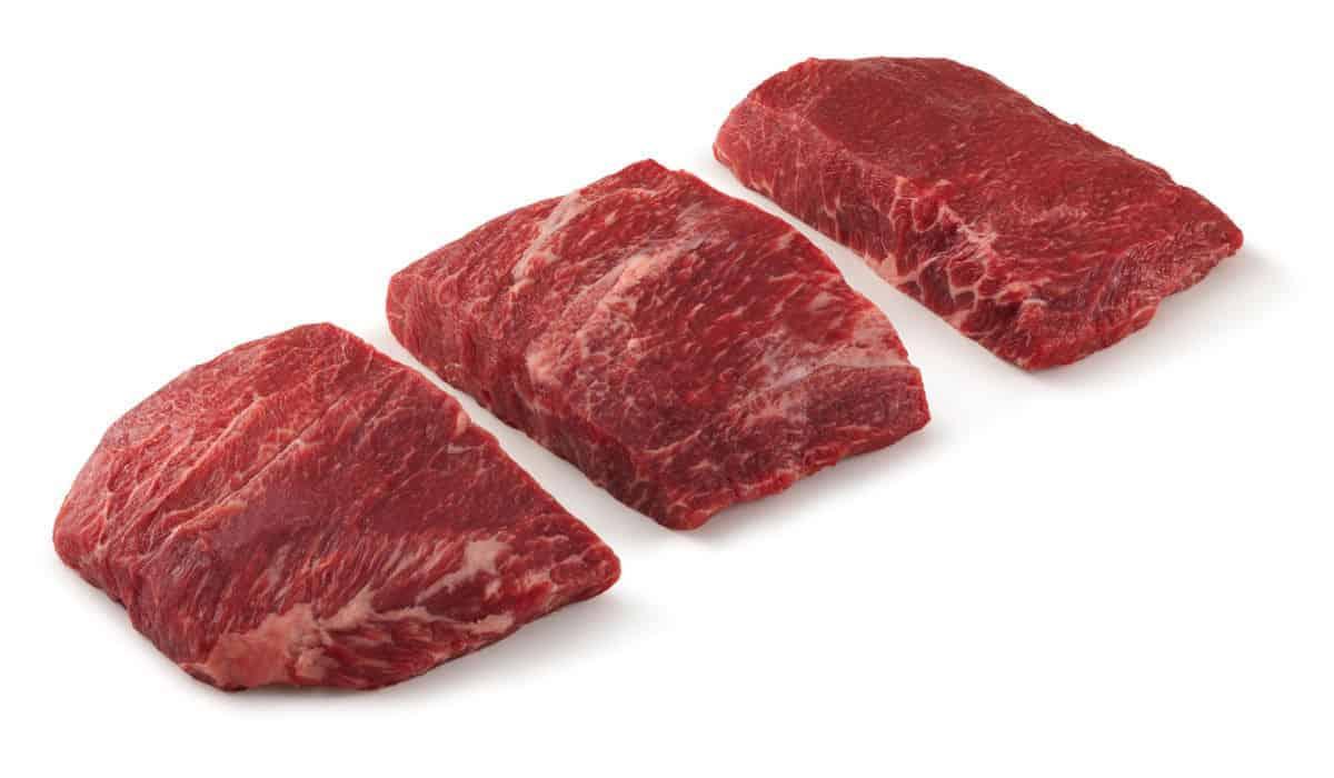Three flat iron steaks isolated on white