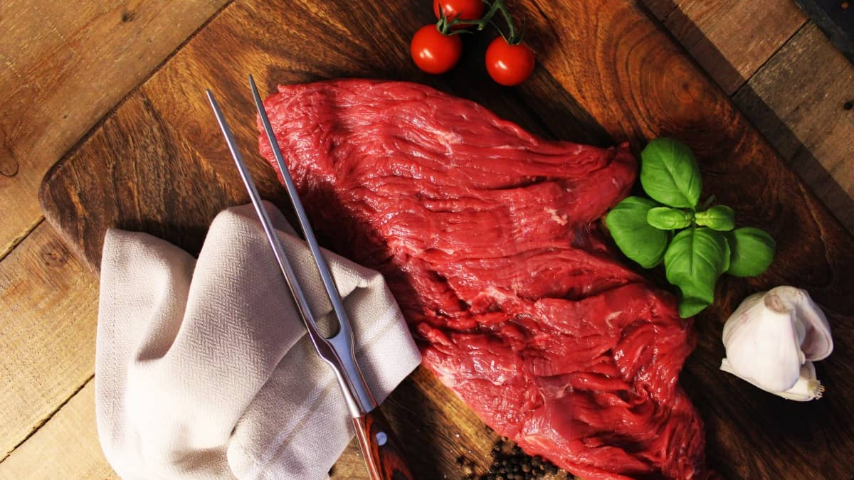 A bavette steak and two pronged fork with tomatoes and basil on cutting board