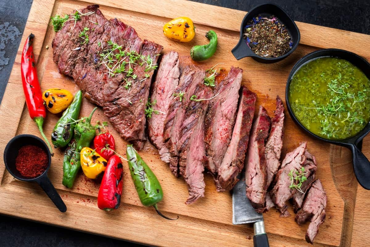 Grilled bavette with salsa verde and grilled peppers on a cutting board