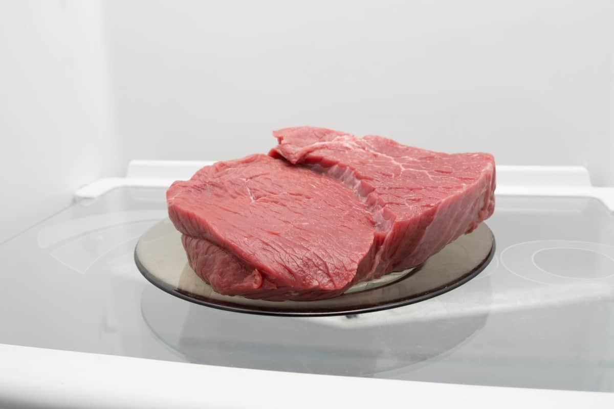 beef on a black plate in an empty fridge