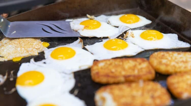 Eggs and hash browns cooking on an outdoor griddle