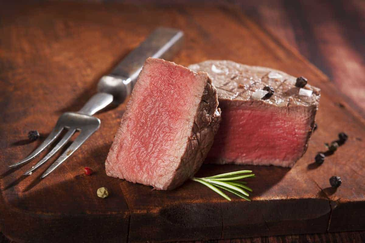 A cooked tenderloin filet mignon, sliced in half on a chopping board