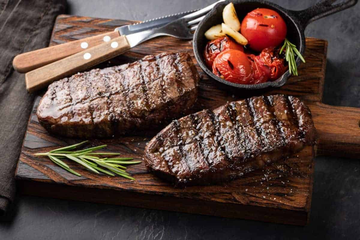Two cooked top blade steaks with tomatoes