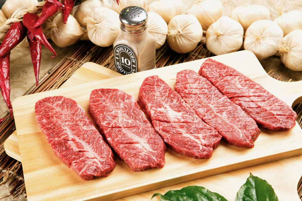 five top blade steaks on a chopping board
