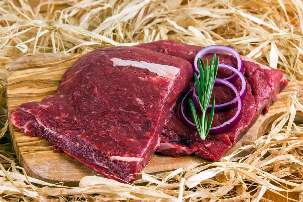 A flat iron steak slice din two, on a cutting boar din hay, with onion slices and rosemary on on ehalf