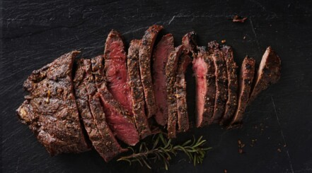 Grilled flat iron steak, sliced and on a black bg