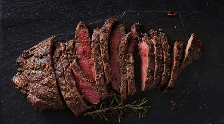 Grilled flat iron steak, sliced and on a black bg