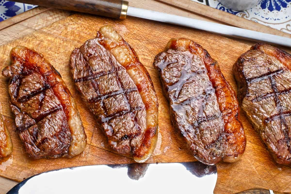grilled picanha steaks laid out on a wooden cutting board with knife and sharpening steel