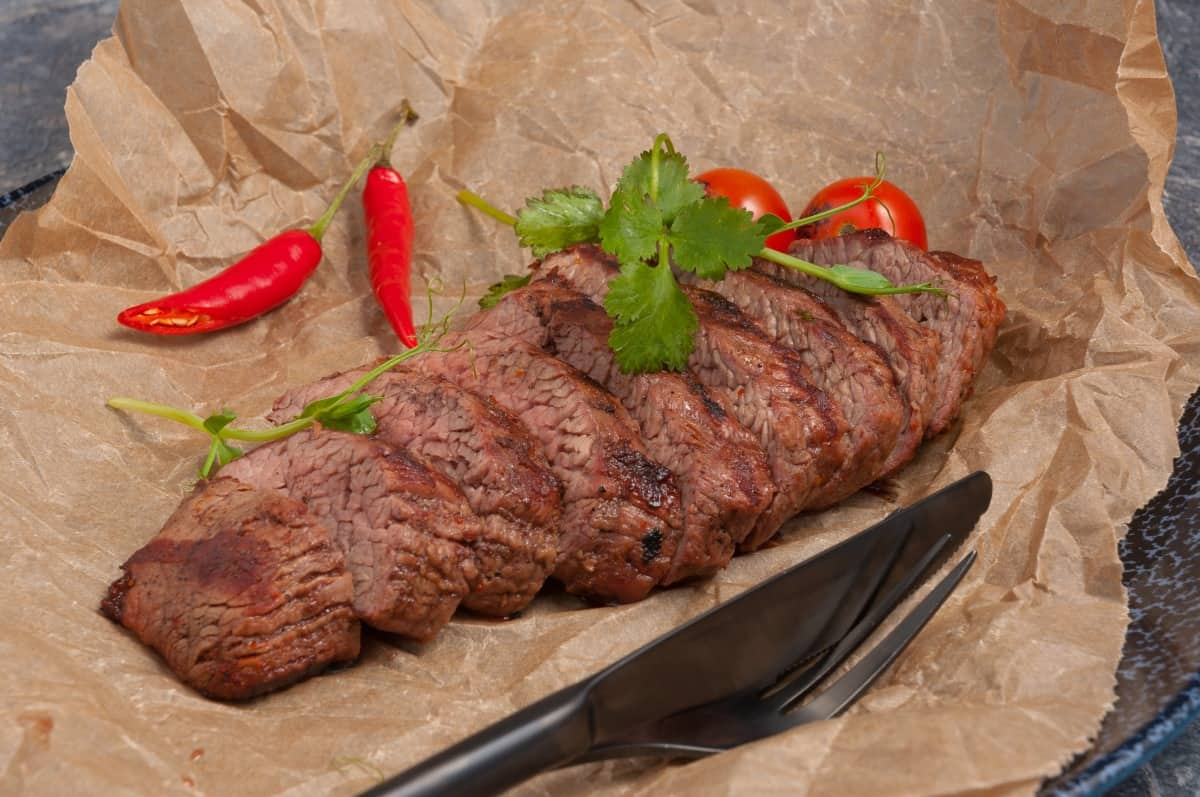 grilled shoulder steak on parchment paper with herbs, tomato and chilis