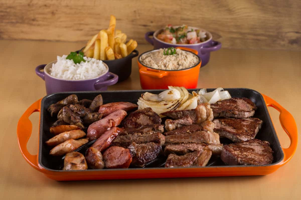 A churrasco platter of picanha, sausage, onion, chips and more