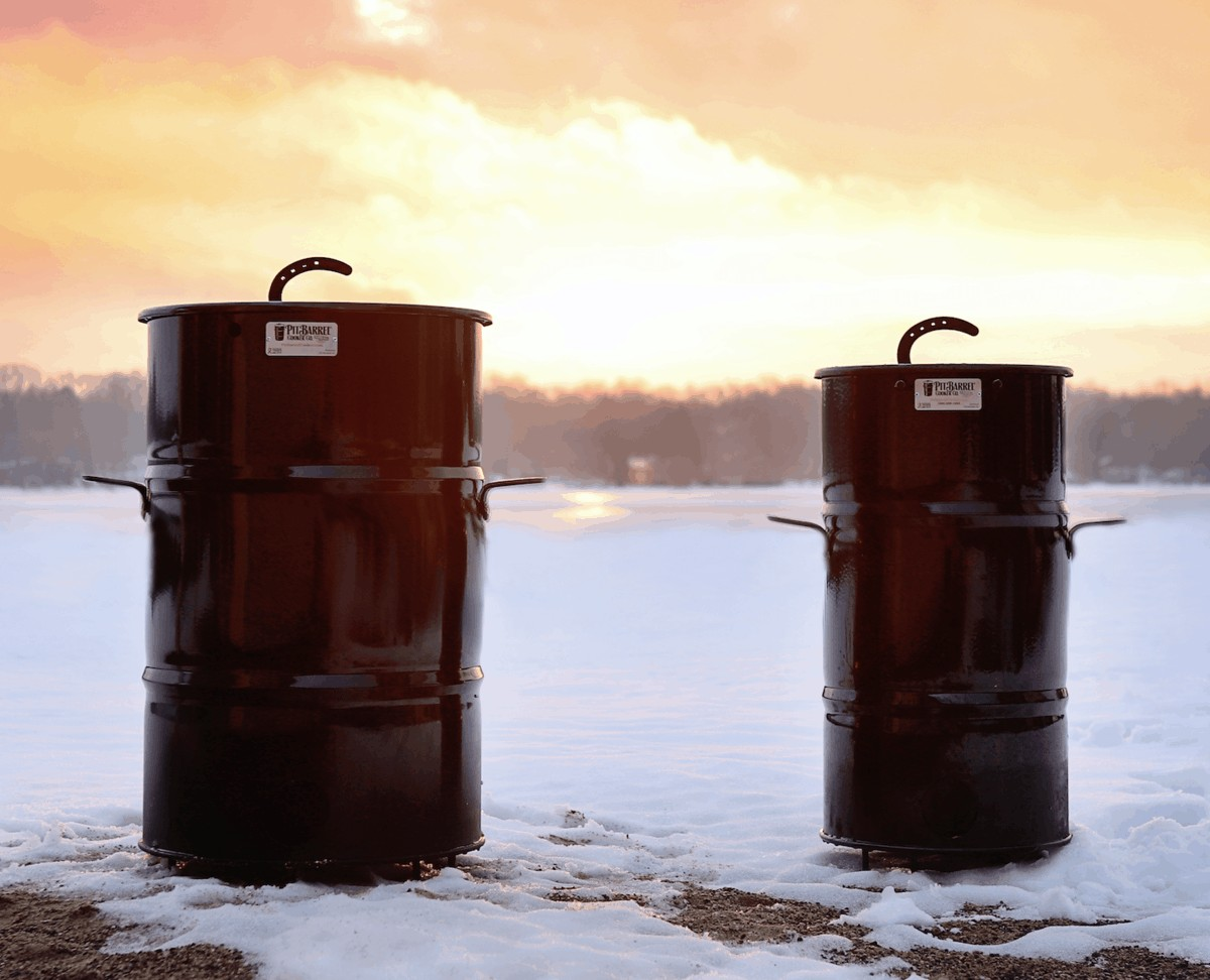 Two pit barrel cookers on snow against a sunny background
