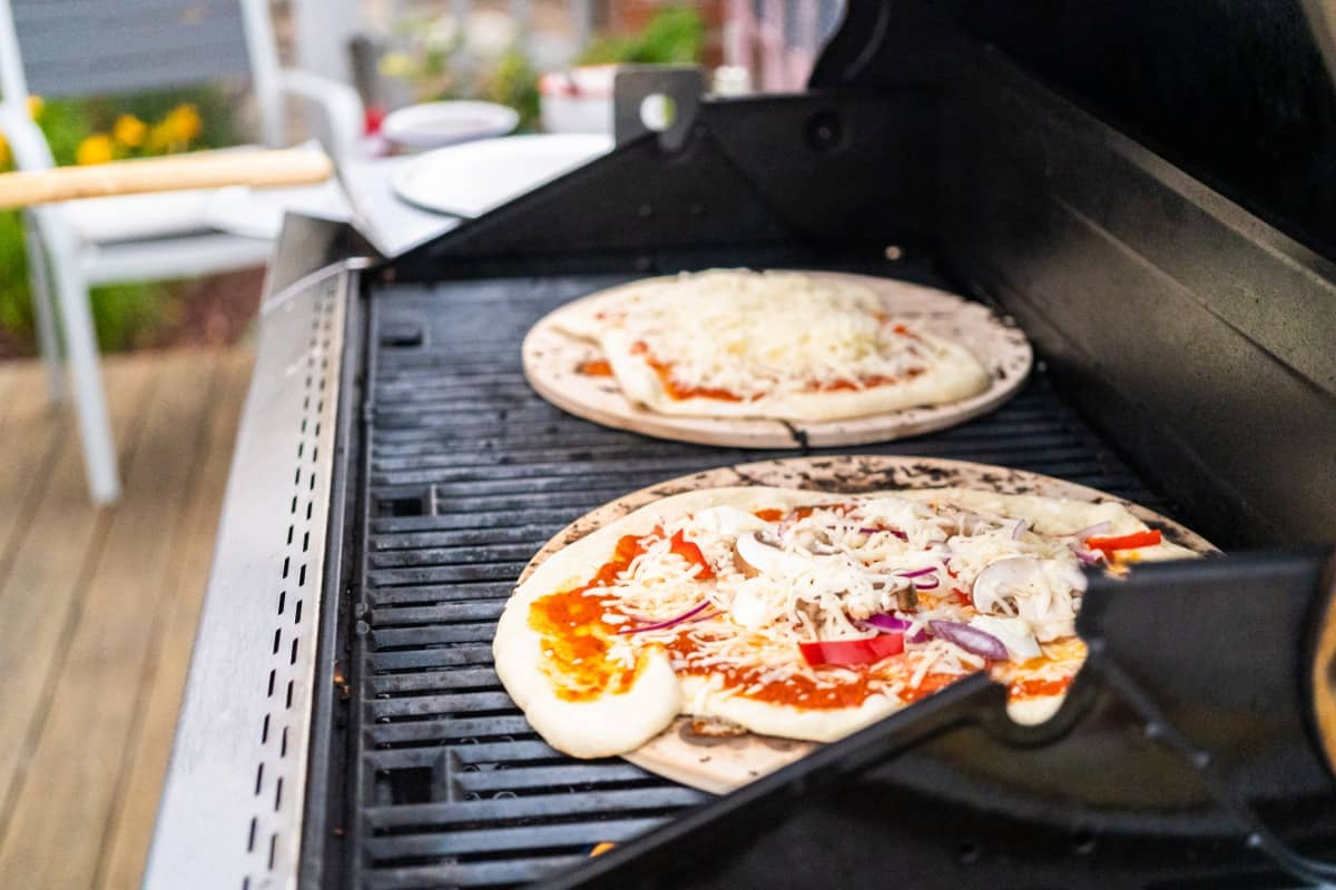 Two pizza stones with pizza on them in a grill
