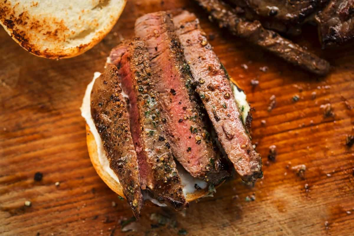 Grilled ranch steak, sliced and placed on half a bun