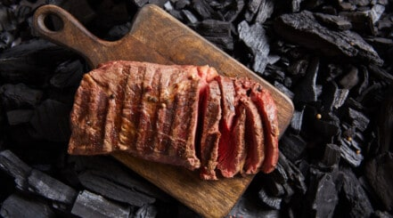 Cooked ranch steak, sliced on a chopping board sitting over charcoal