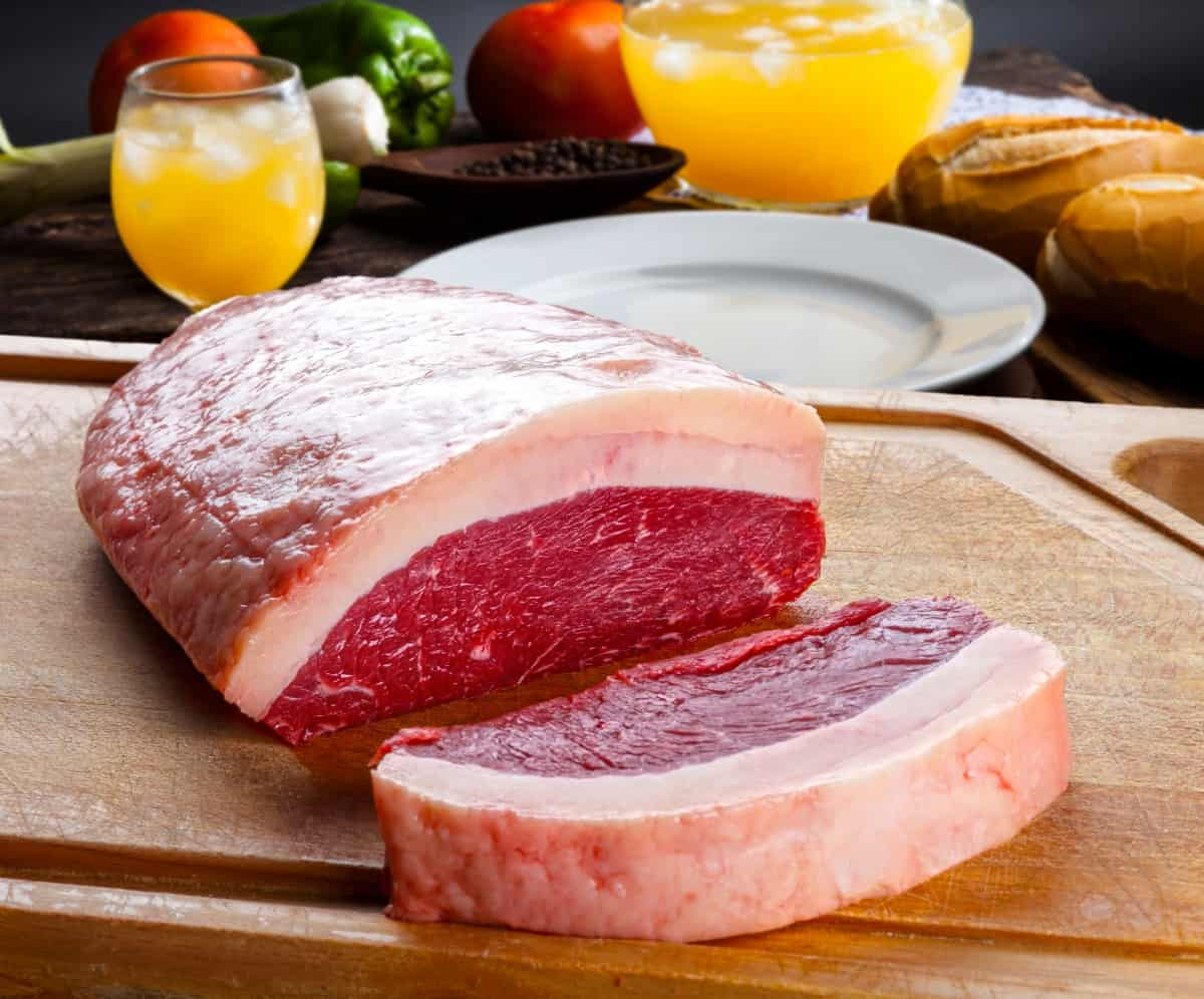 raw picanha joint with a steak sliced off, sitting on a cutting board in front of blurred vegetable background