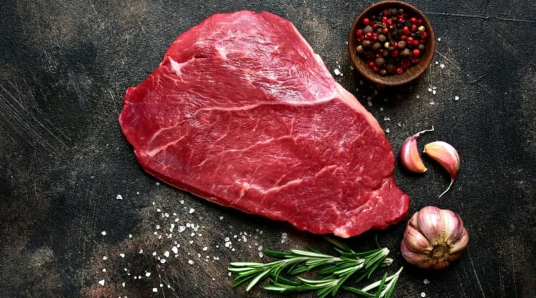 A raw shoulder steak on a dark surface with rosemary sprigs