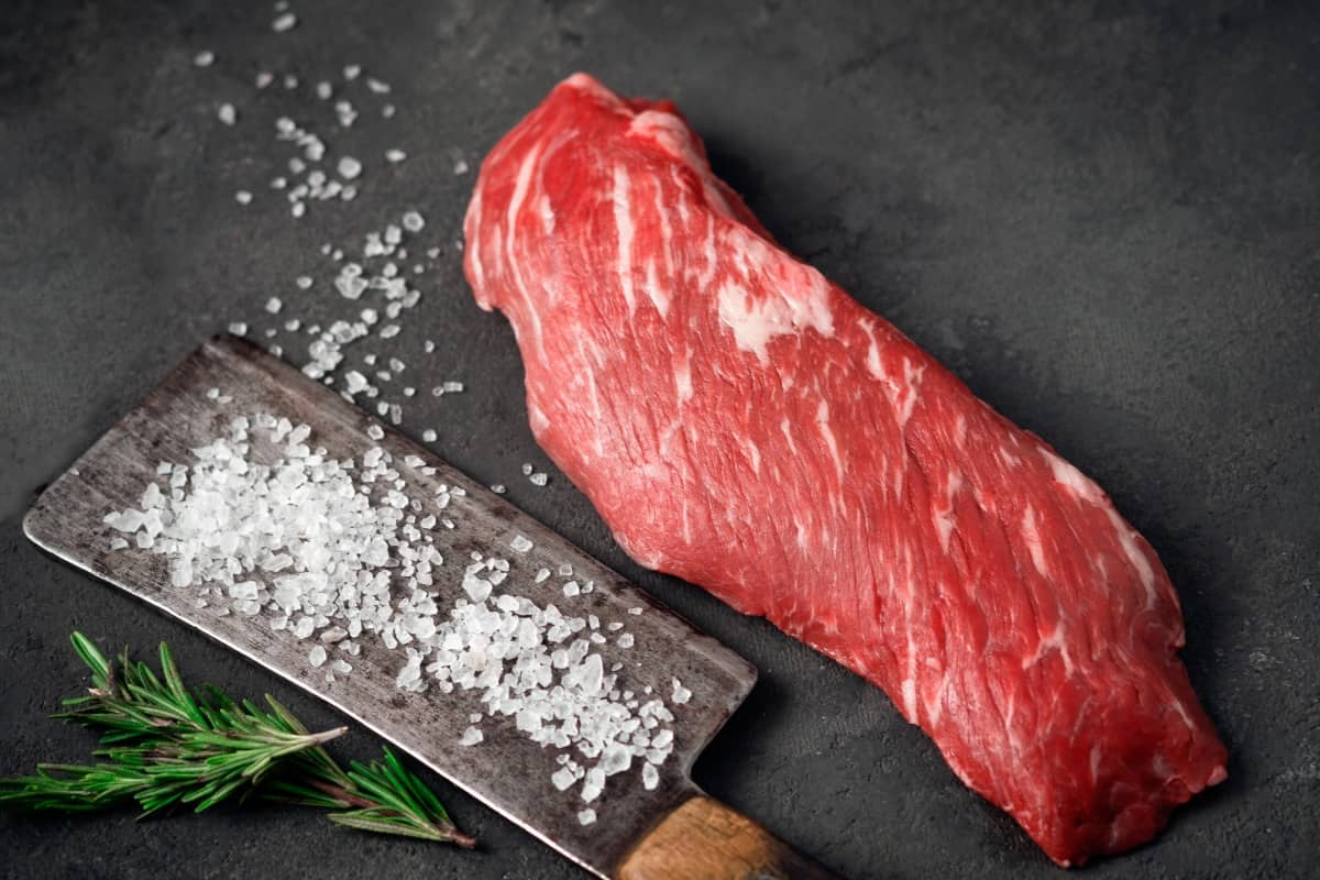 A raw skirt steak next to a meat cleaver covered with salt
