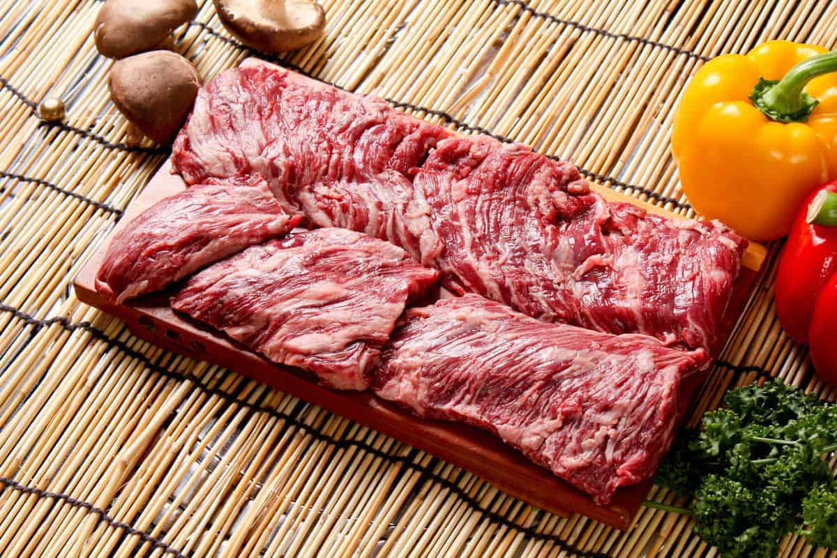 Two uncooked skirt steaks on a wooden cutting board