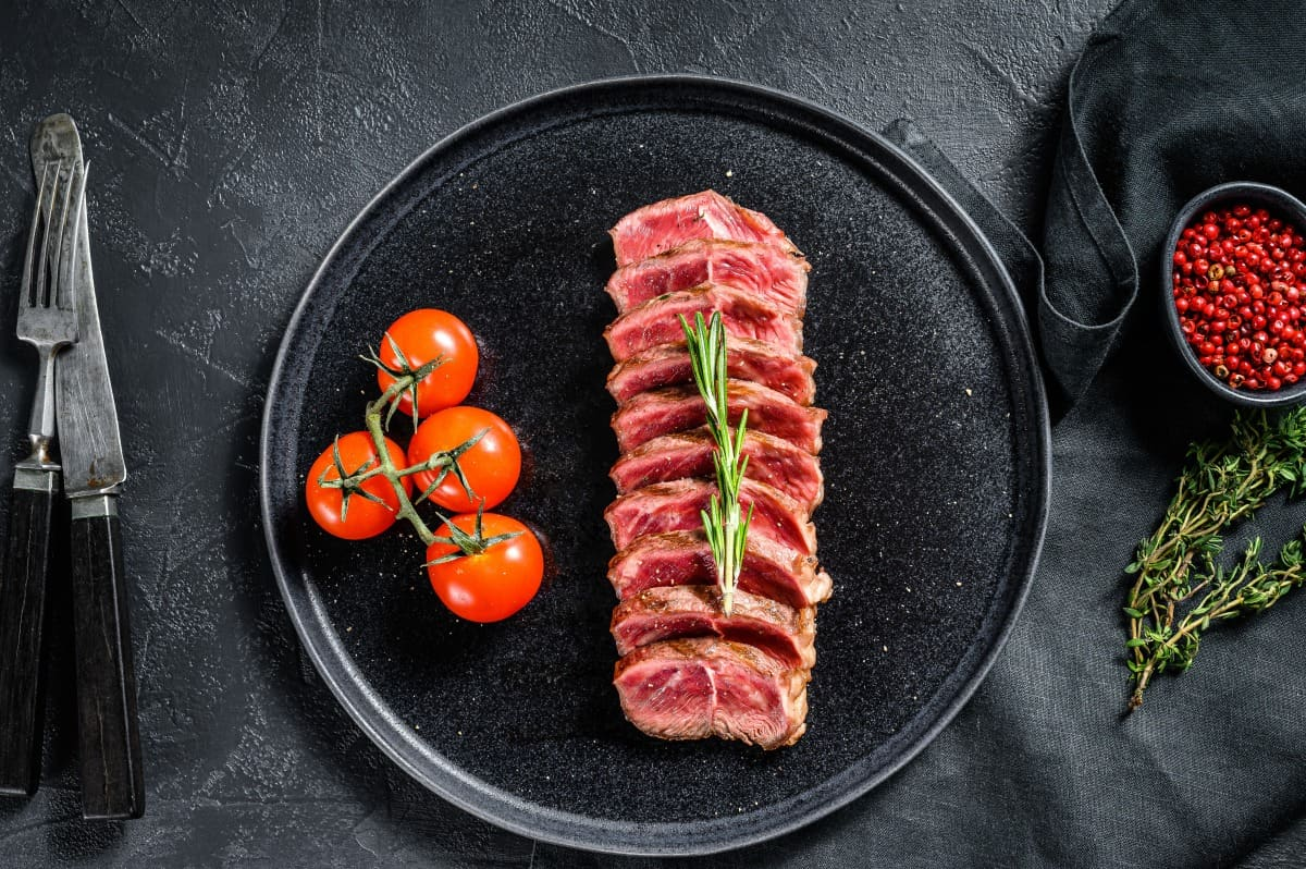 sliced grilled top blade steak on a black plate with some cherry tomatoes