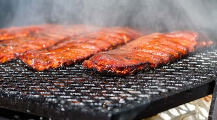 Racks of ribs laying flat in a barbecue smoker