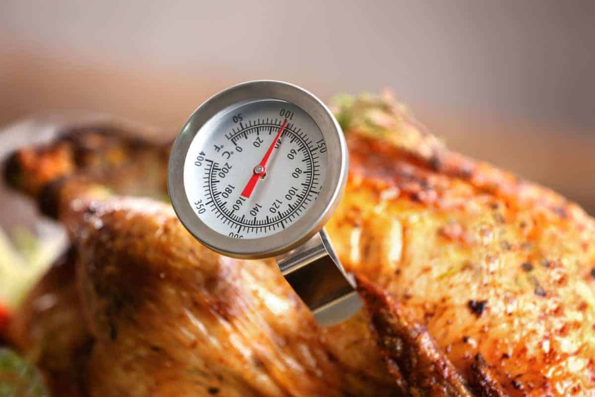 An analog thermometer taking the temp of a chicken