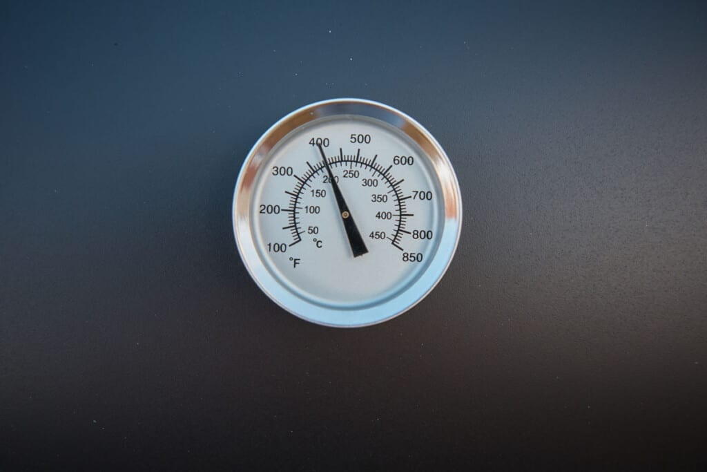 A close up of a smoker thermometer on a black barbecue
