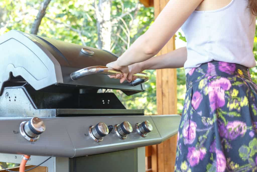 Young woman closing the lid on an IR grill