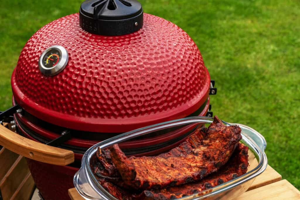 A red kamado grill with some rubbed ribs on it's side shelf