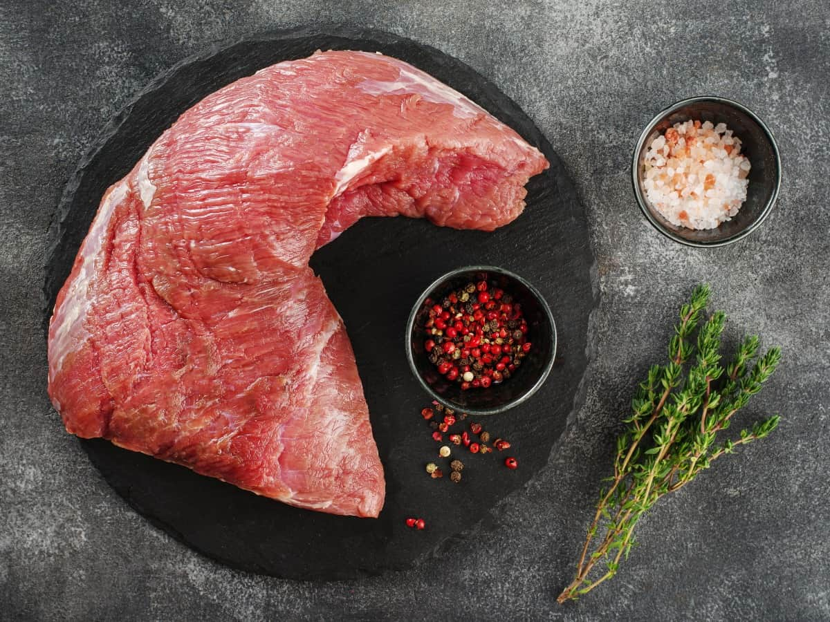 Raw beef tri-tip on a black plate with a pot of dry rub