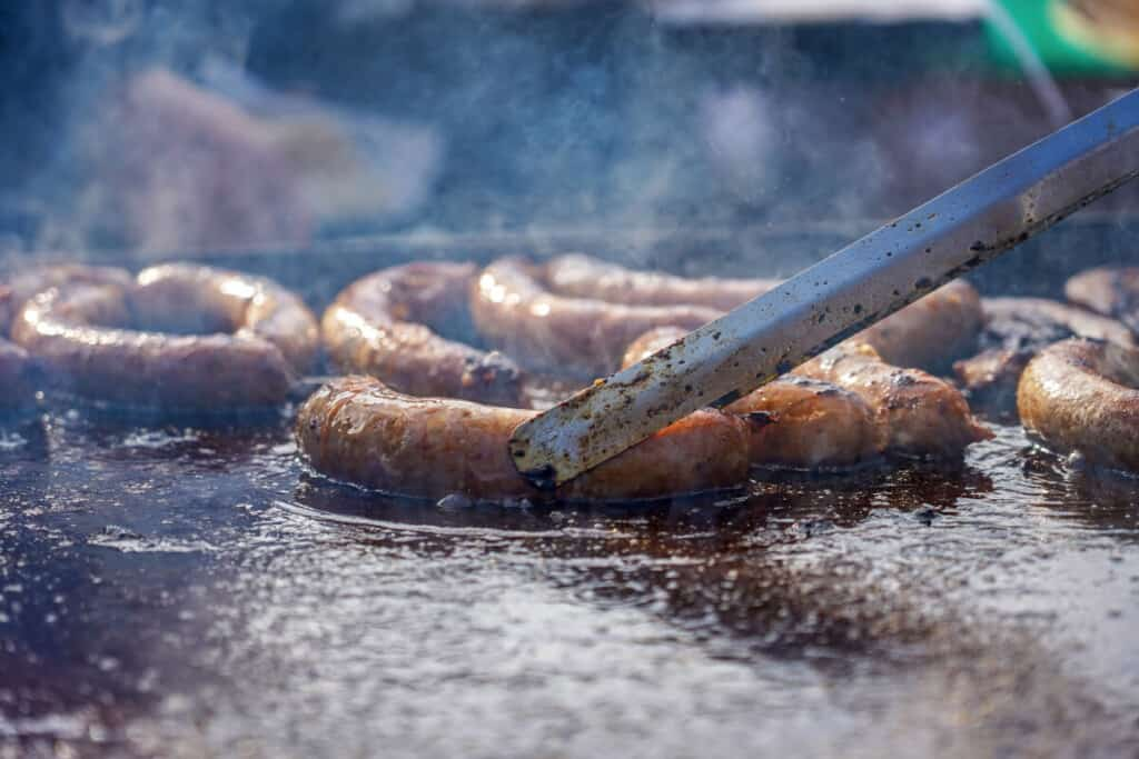 Sausages being cooked on a griddle