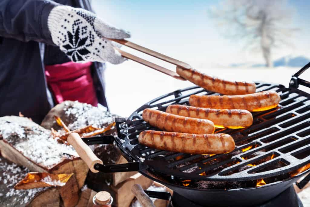 A person wearing BBQ gloves moving sausages around a hot grill.