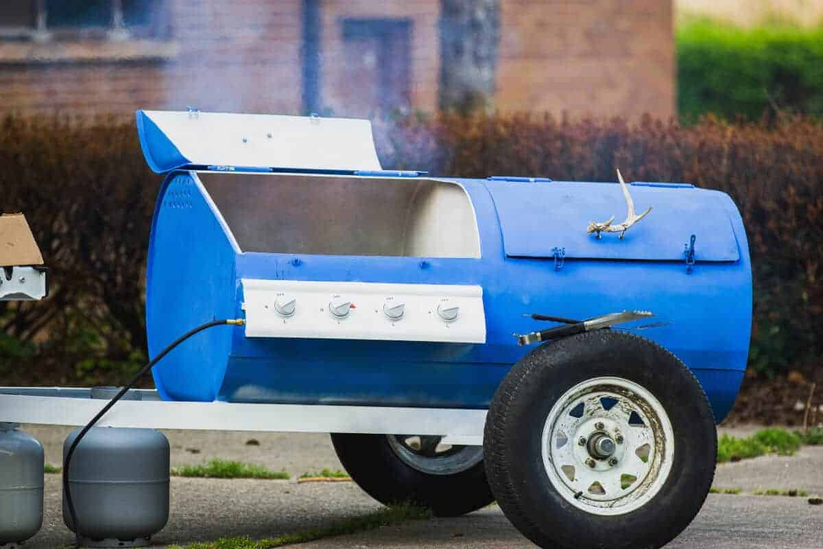 A big, blue, trailer pulled gas and charcoal combo grill