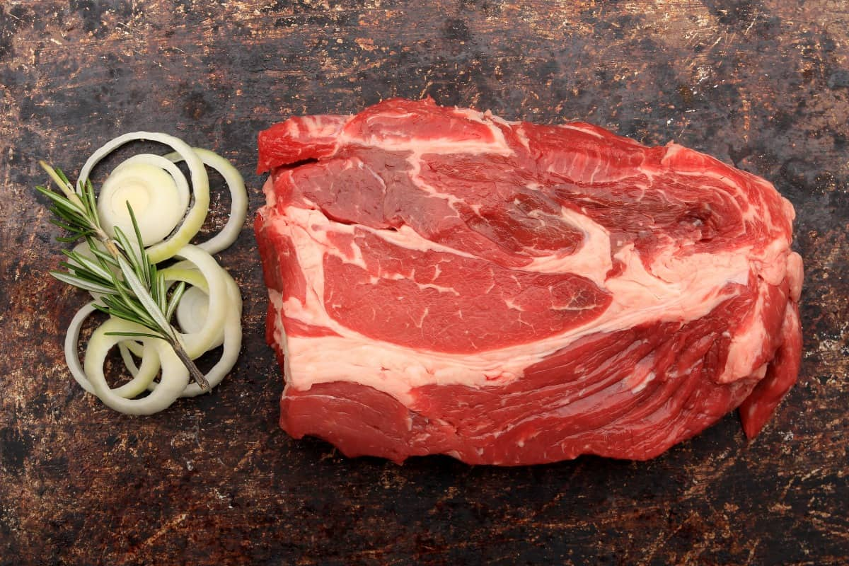 A raw blade chuck steak with sliced onions