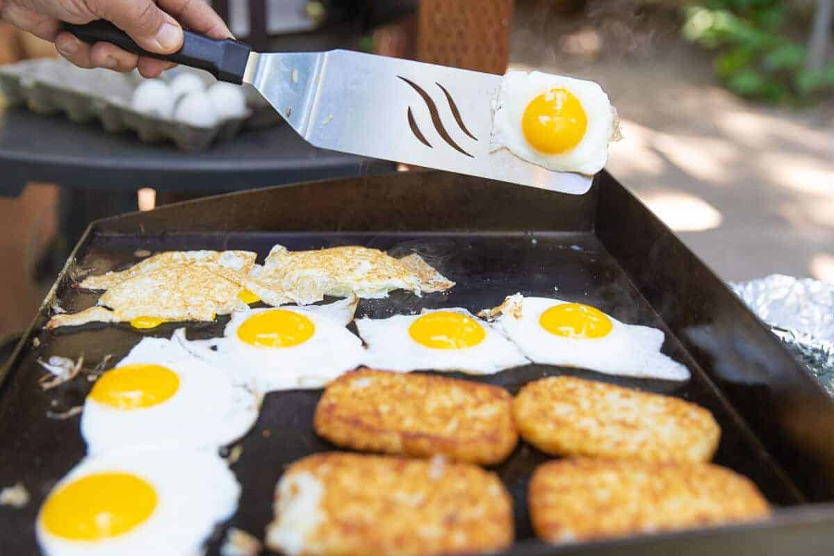Breakfast of eggs and hash browns being cooked on a flat top griddle
