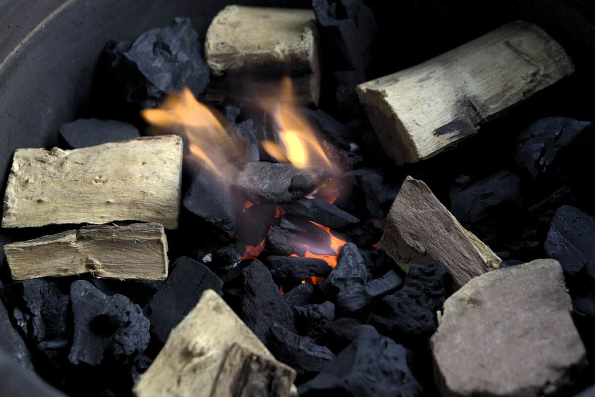 A close up of wood on top of smoldering charcoal inside of a smoker