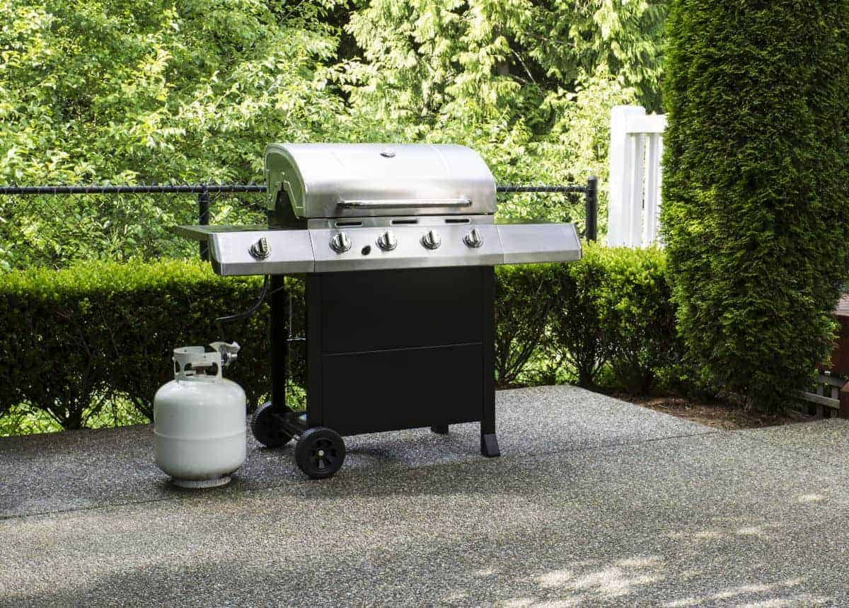 A propane gas grill with cylinder beside it
