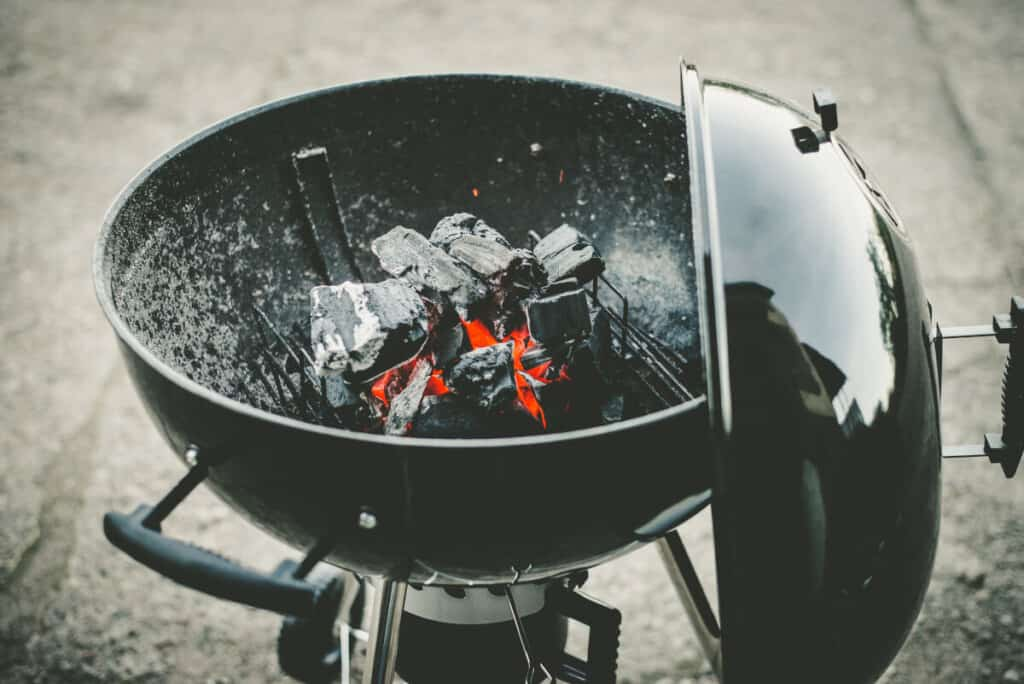 A lit, circle shaped charcoal grill with the lid hanging from the side