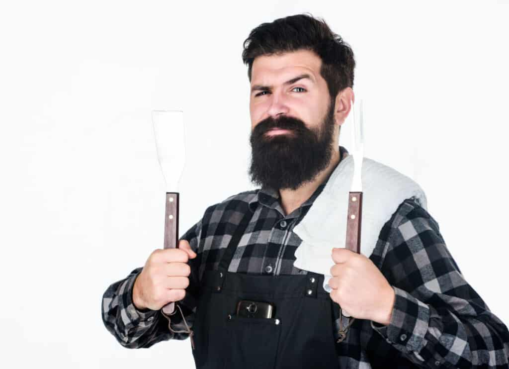 A bearded man holding two grilling tools isolated on white