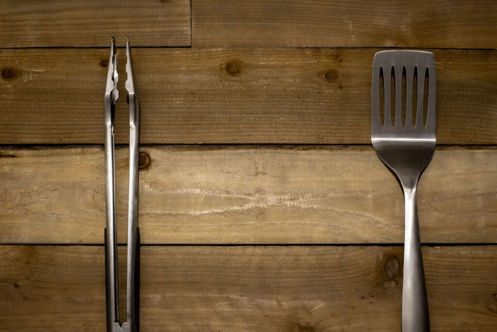 Spatula and tongs on a wooden surface