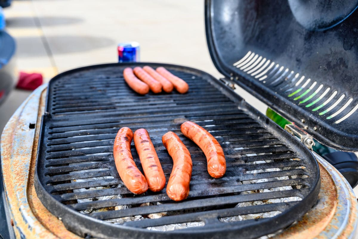 Hotdogs cooking on a portable gas grill