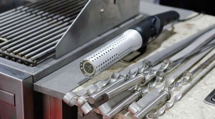Grilling accessories, a looftlighter and some kebab blades, next to a high quality, stainless steel grill