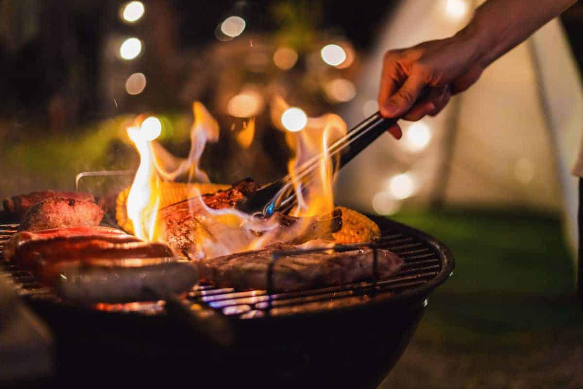 A hot, flaming grill at night while camping