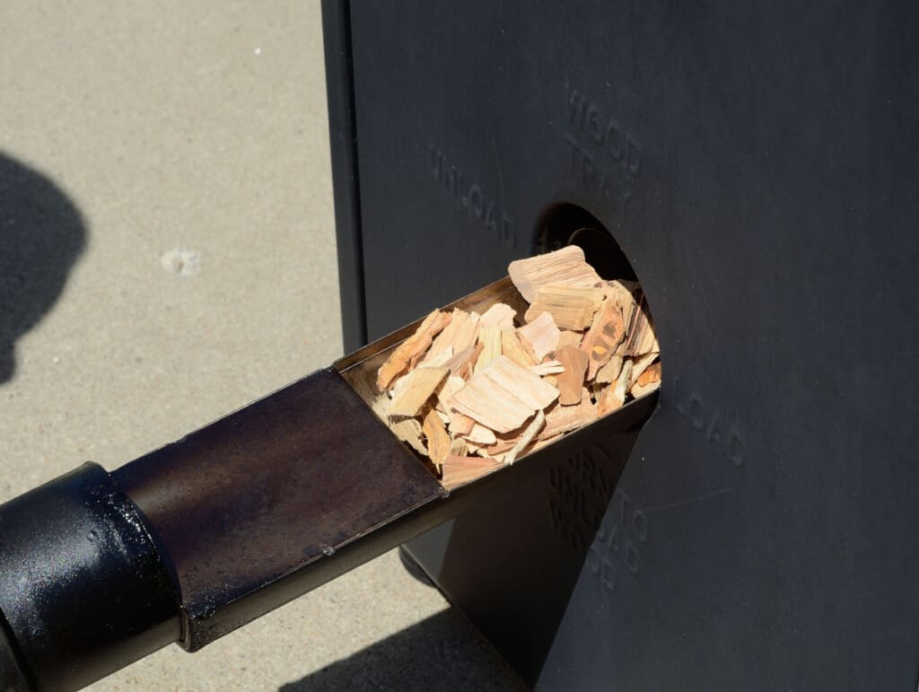 Wood chips being placed into the side of an electric smoker