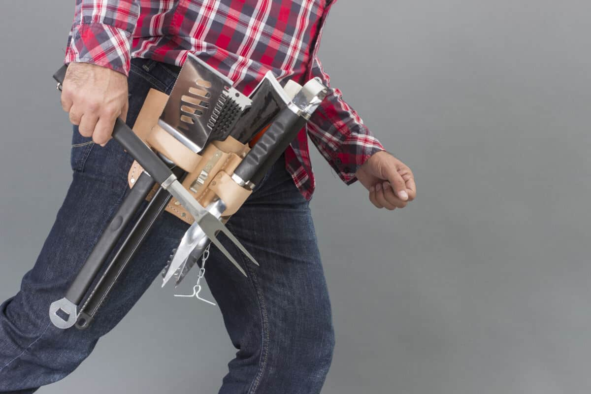A man with a full tool belt of grilling tools