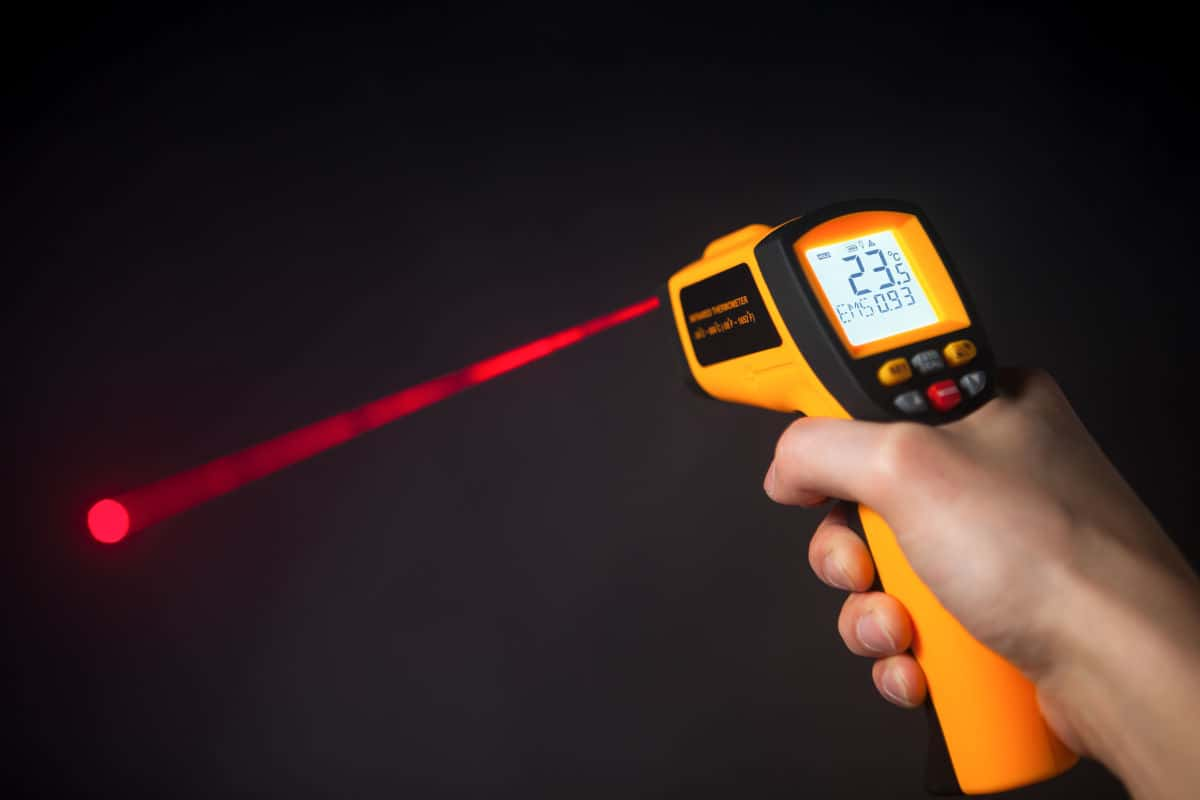 An infrared thermometer firing a red laser onto a black surface to take temp