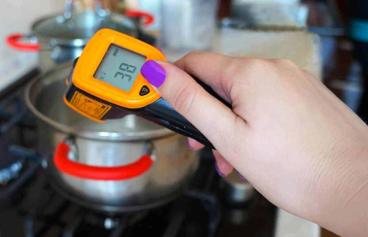 An infrared thermometer measuring the heat from a pan on a hob