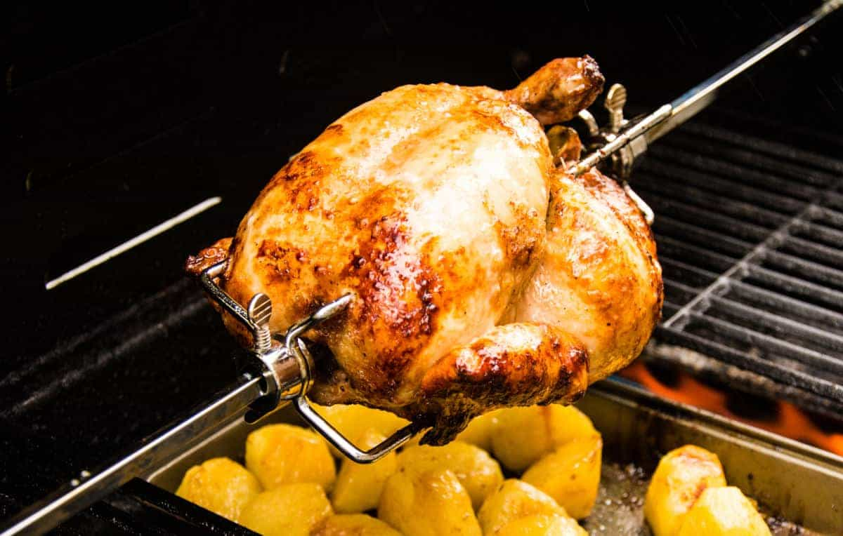 Z chicken being cooked rotisserie, with drippings going onto potatoes