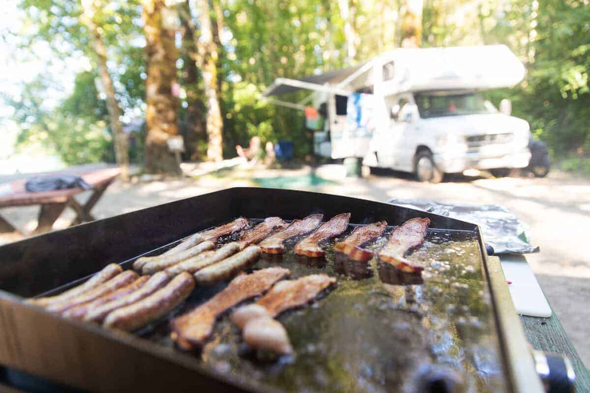 A portable flat top grill cooking bacon, with an RV in the background