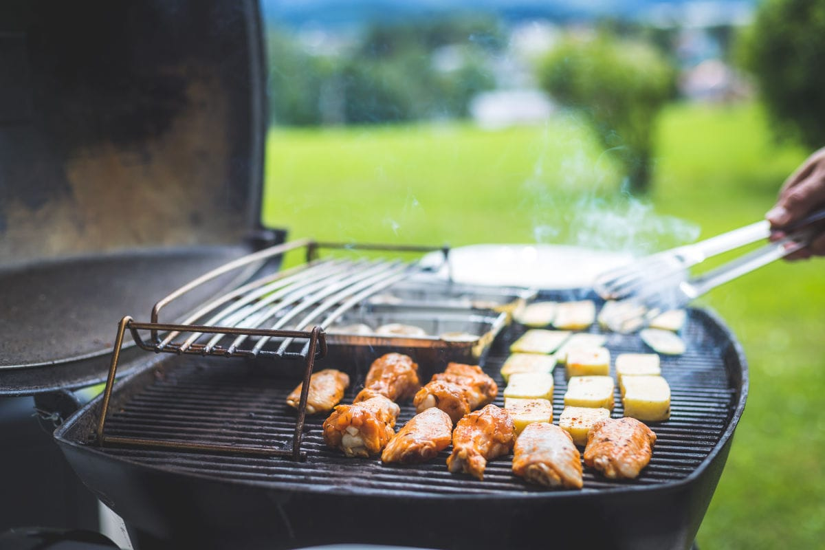 Close up of chicken and vegetable son a gas grill, in a field